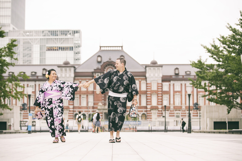 Pre-wedding photo of a couple walking hand in hand in front of Tokyo station wearing kimono