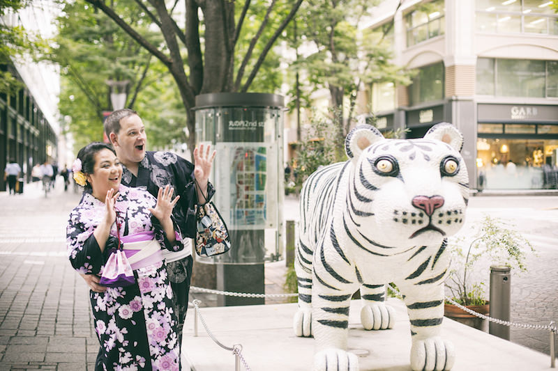 Pre-wedding photo of a couple wearing kimono and posing at the tiger statue in Marunouchi, Tokyo