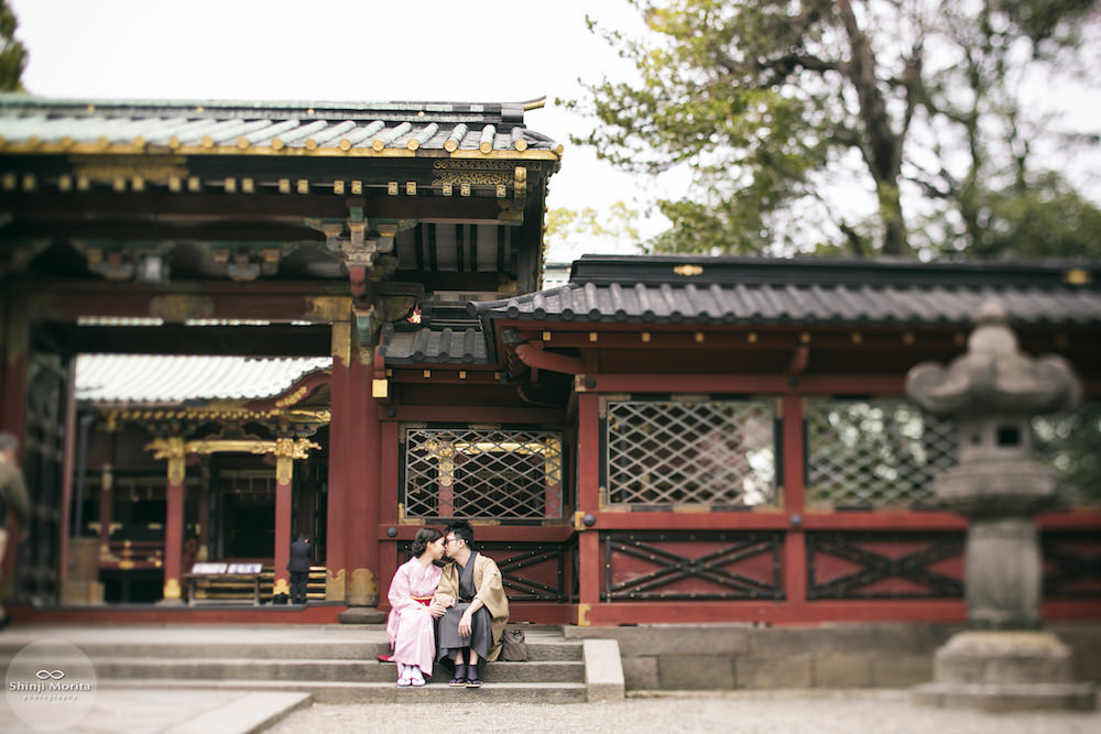 Pre-wedding photo of a couple sitting in front of the shrine in Nezu