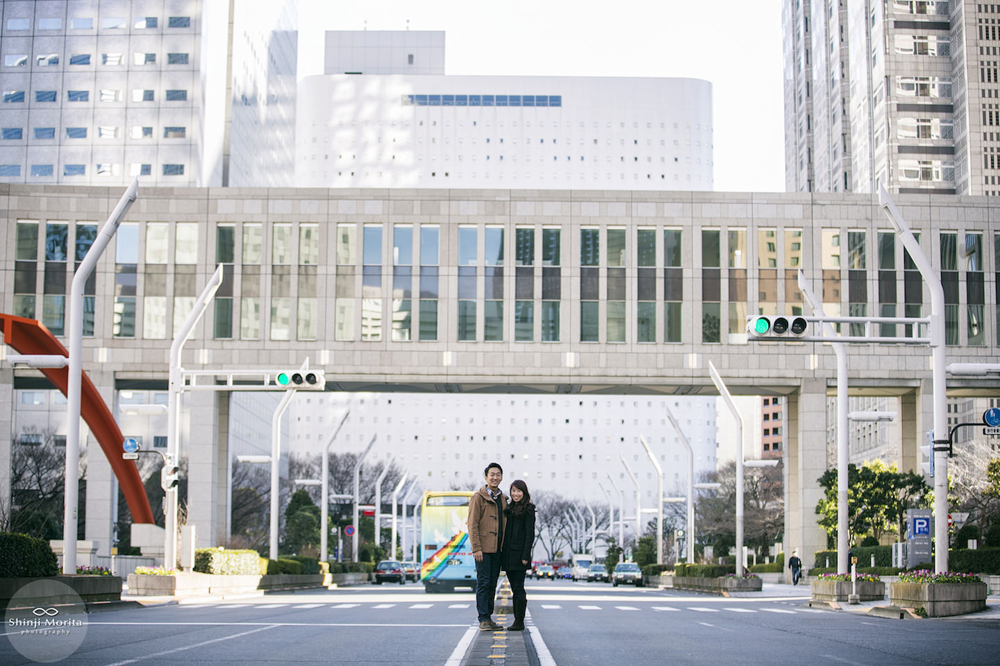 A couple smiling at the camera by the Tokyo Government office in Shinjuku