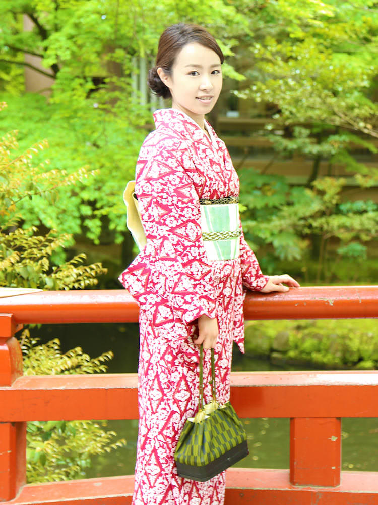 A woman posing at the bridge in Kyoto wearing a red kimono