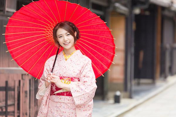 A woman holding a Japanese umbrella wearing pink kimono