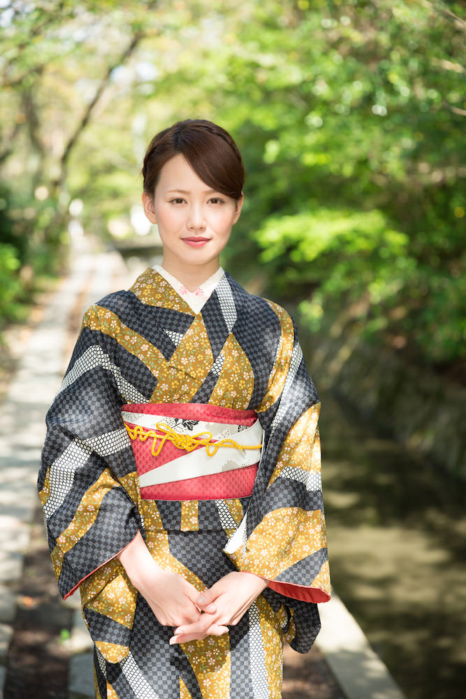 A woman posing with black and gold patterned kimono in Kyoto