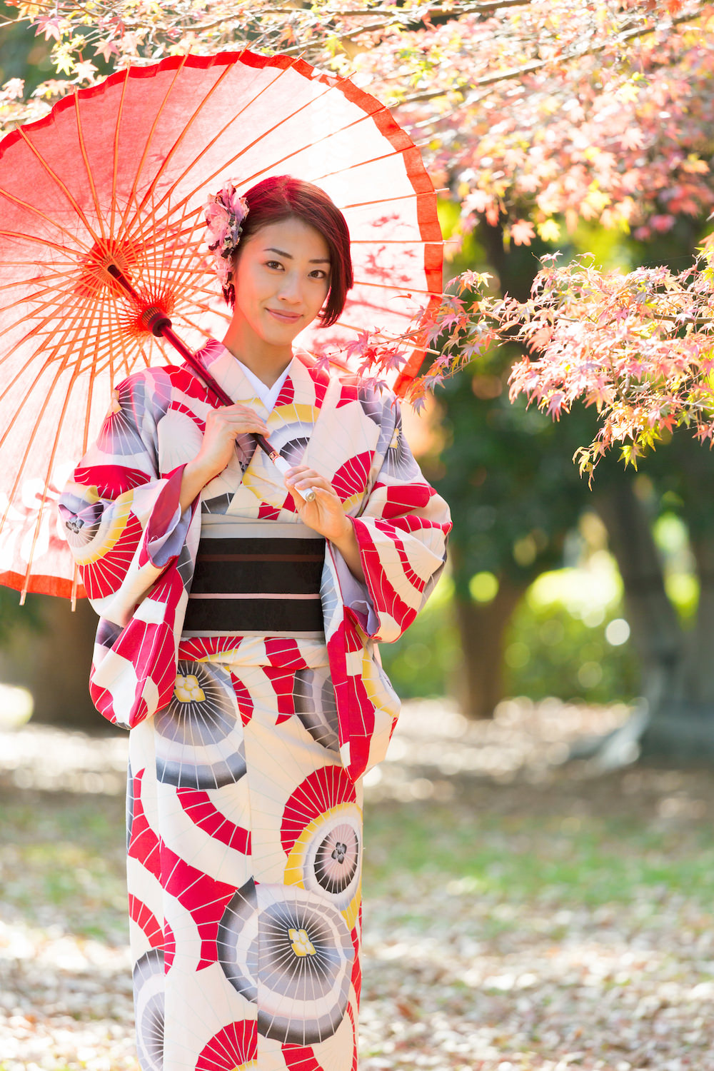 A woman holding a Japanese umbrella wearing a modern patterned kimono