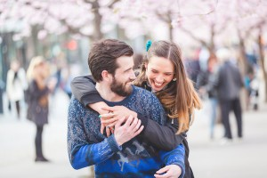 Couple hugging and being playful with cherry blossoms in the backgourd
