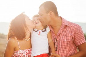 Happy family with mom and dad kissing their child during vacation photo