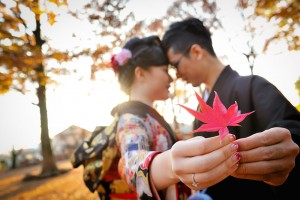 A couple holding a red maple leaf during their pre-wedding photo