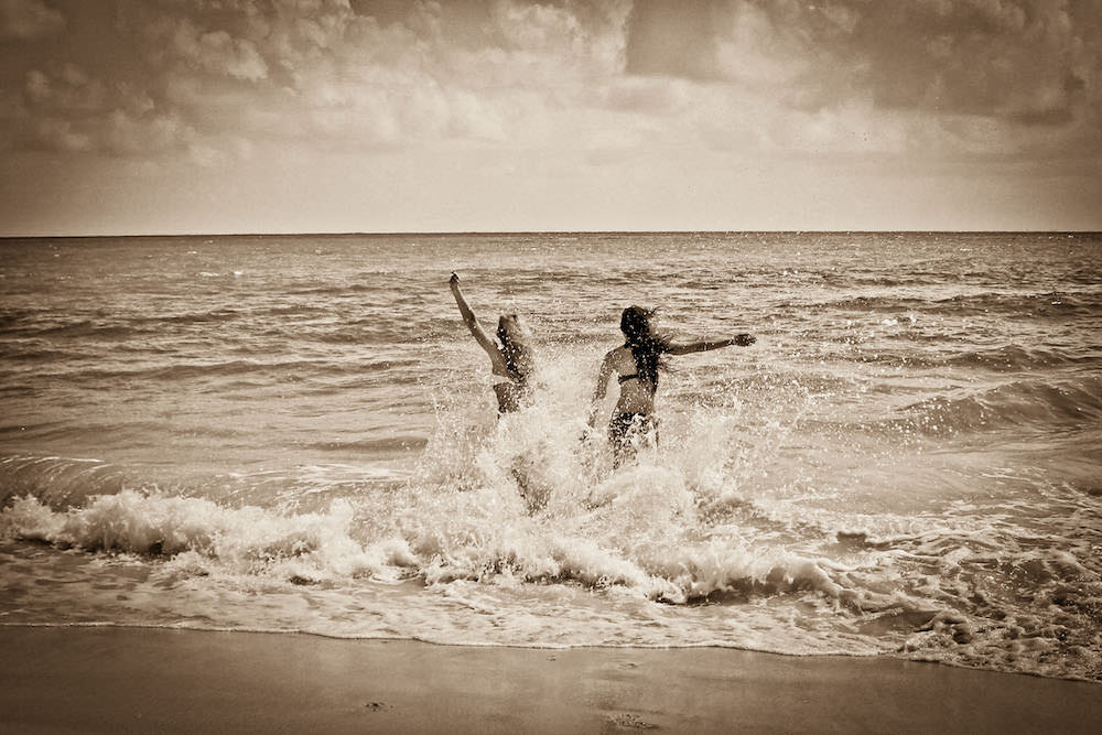 Vacation photo of two women being playful at the beach