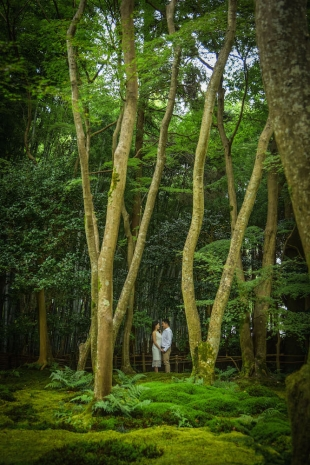 Vacation photo of a couple looking at each other surrounded by beautiful moss garden in Arashiyama, Kyoto