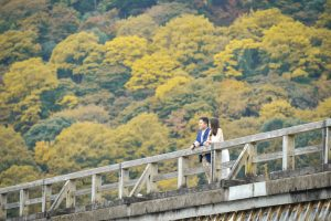 Vacation photo of a couple looking at Hozu river from Togetsukyo bridge in Arashiyama, Kyoto