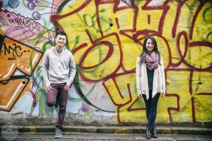 A couple smiling at the camera in front of a spray painted wall in Harajuku, Tokyo
