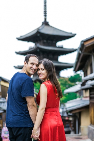 A couple looking back to the camera with five story pagoda in the background for vacation photo with Yusuke HImi
