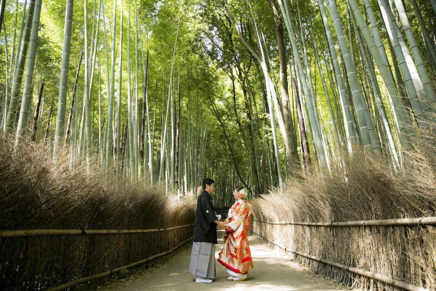 A couple looking at each other surrounded by bamboo forest in Arashiyama for pre-wedding photo