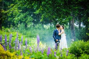 Photo by Masayuki of a couple kissing surrounded by beautiful flower garden at a park in Hokkaido