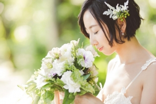 A woman enjoying the smell of her flower bouquet during pre-wedding photo with CHiKA