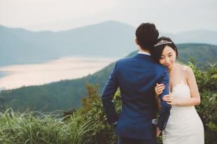 A woman holding on tight to her fiancé at Hakone mountain for pre-wedding photo with CHiKA