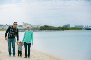 Family vacation photo as the family walks along the beach of Okinawa