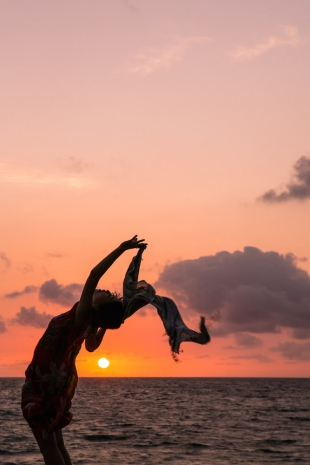 A woman leaning back with beautiful sunset in the background for vacation photo with Yoshiaki Ida