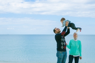 Family vacation photo as the father lifts his baby boy up in the air with beautiful ocean of Okinawa in the background
