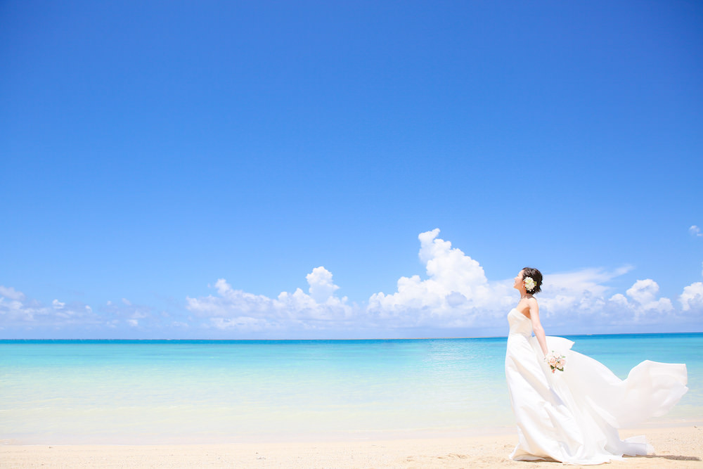 A woman dressed in wedding gown posing at the beach in Okinawa for pre-wedding photo with Yoshiaki Ida