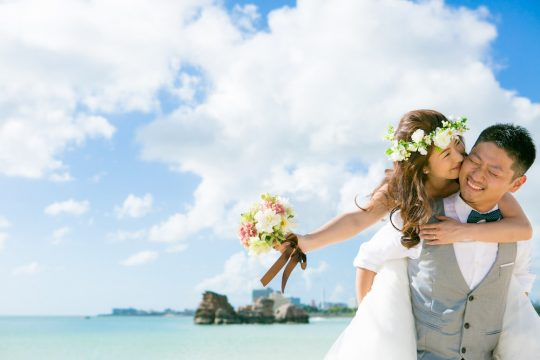 A lady kissing his fiancé while being piggybacked at the beach in Okinawa for pre-wedding photo with Yoshiaki Ida