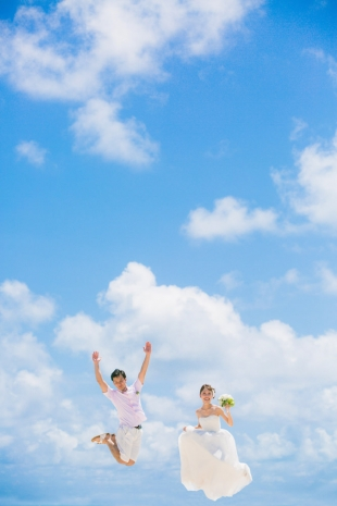 A couple jumping up to the blue sky in Okinawa for pre-wedding photo with Yoshiaki Ida