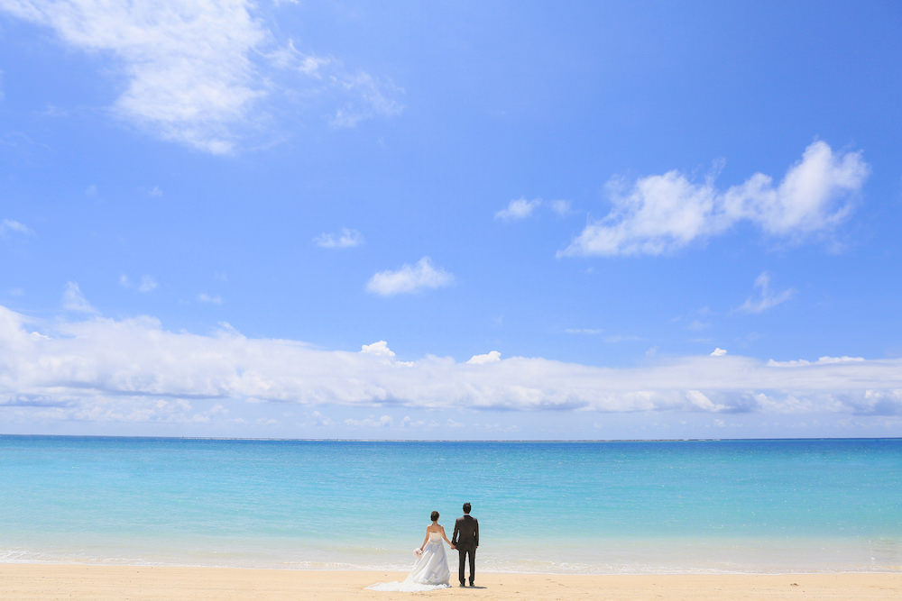 A couple looking at the beach during sunny day for pre-wedding photo with Yoshiaki Ida