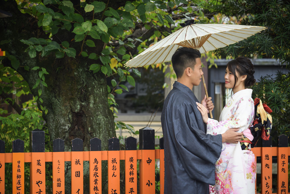 Pre-wedding photo of a couple smiling at each other romantically holding Japanese umbrella in Gion, Kyoto