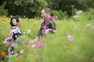Pre-wedding photo of a couple holding hands surrounded by cosmos flowers in Hamarikyu garden, Tokyo