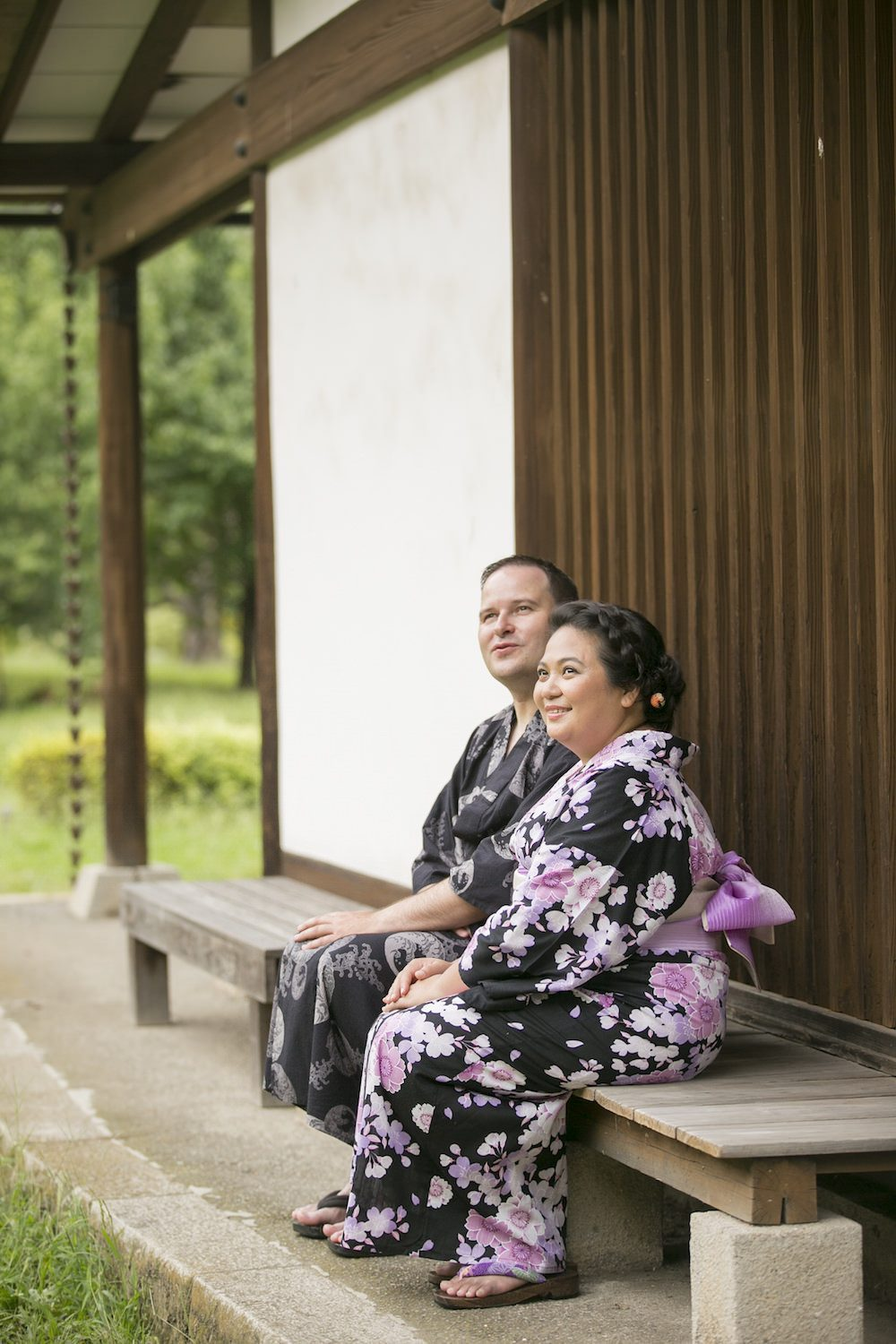 Pre-wedding photo at Hamarikyu garden in Tokyo with a couple sitting in front of a traditional Japanese style house