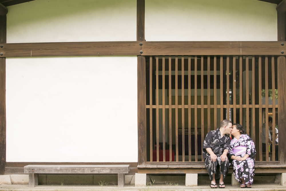 Pre-wedding photo of a couple kissing in front of a traditional Japanese building